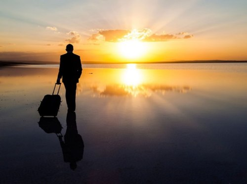 man-beach-sunset-suitcase